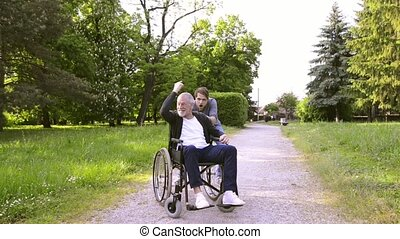 Hipster son with disabled father in wheelchair in park.