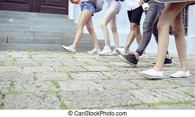 Unrecognizable teenage students walking to university. -...