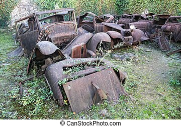 Rusty cars in the destroyed village of Oradour sur Glane in...