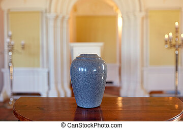 cremation urn on table in church - funeral and mourning...