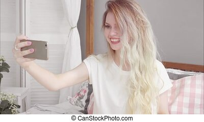 Young attractive blonde woman speak video call on smartphone...