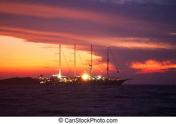 Boat sailing at dusk on the aegean sea