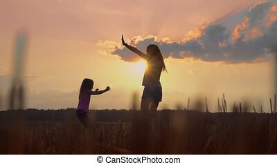 Mom and daughter jump and dance at sunset. Slow Mo