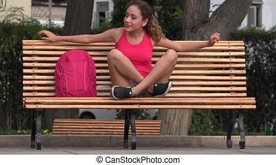 Happy Female Student Sitting On Park Bench