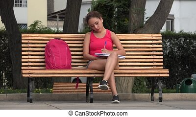 Female College Student Writing In Notebook Sitting On Park Bench