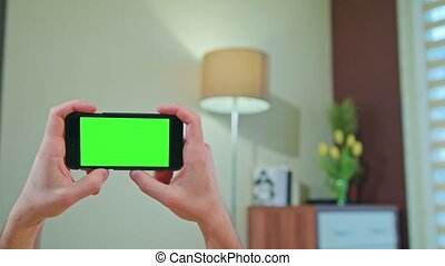 Male Hands Holding a Phone with a Green Screen