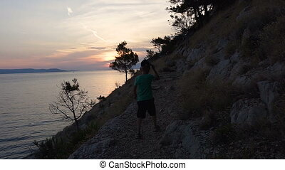 A good guy comes from the beach on a rocky mountain overlooking the sea and admiring the sunset. Dalmatia. Croatia