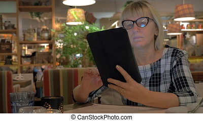 Senior woman browsing on touch pad in cafe - Senior woman in...