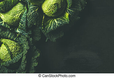 Raw fresh uncooked green cabbage over dark background, copy...