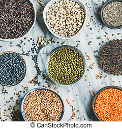 Various raw uncooked grains, beans, cereals, marble...