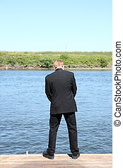 Man peeing in the river - Man in suit peeing in the river.