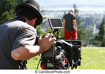 Man with digital cinema camera on movie set.