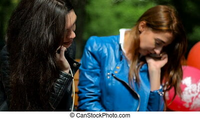 girlfriends sit in the Park and talking on mobile phones -...