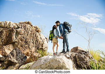 Kissing on the mountaintop - Cute couple standing on a rock...