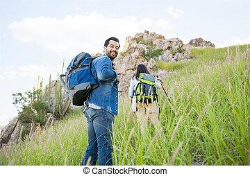 Hiking to the mountaintop - Cute Latin couple climbing a...
