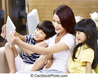 asian mother and children taking a selfie at home - young...