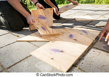 Cropped Image Of Friends Arranging Wooden Puzzle On Patio -...