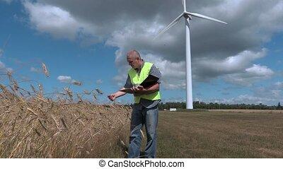 Farmer checking cereals near wind turbine