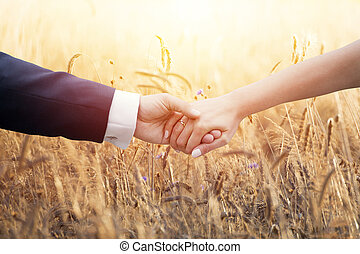 Wedding couple holding hands over ears of corn