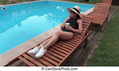 Woman with a cup of coffee at the pool