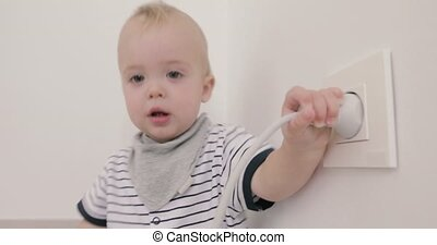 Baby boy playing with plug and socket - Curious little boy...