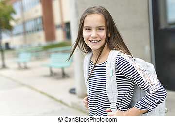 Elementary school pupil outside carrying rucksack - An...