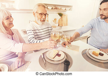 Cheerful aged couple and his son enjoyign family celebration...