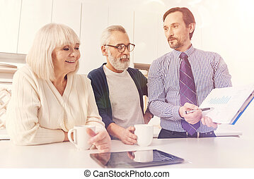 Positive aged couple meeting with real estate agent -...