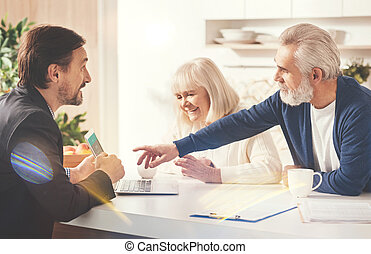 Positive old couple meeting with their insurance agent -...