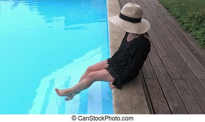 Woman in straw hat relaxing on the edge of swimming pool