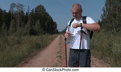 Tired hiker with bottle of water on rural road