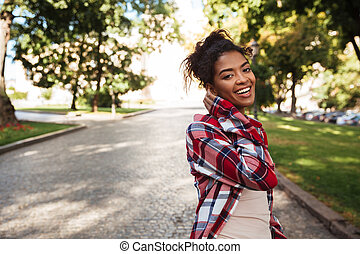 African woman walking outdoors in park. Looking camera. -...