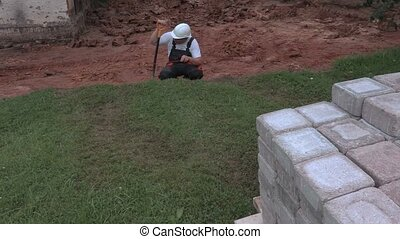 Builder with spade checking level