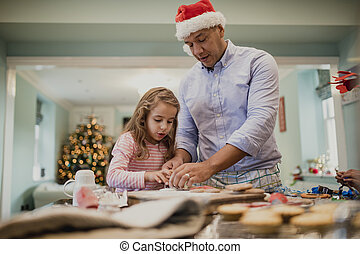 Making Chritmas Biscuits With Dad - Little girls are making...