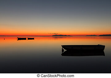 A warm sunset on a calm water, with Islands in the...