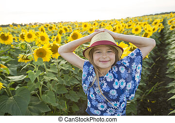 happy girl on a field of sunflowers on summer sunset - A...