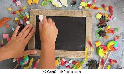 Hands writting trick or treat on blackboard, halloween scene