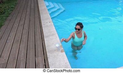 Woman with a cocktail at the edge of the pool