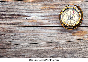 old-fashioned brass compass on rustic wooden table