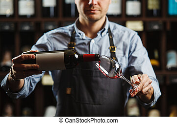 Male sommelier pouring red wine into long-stemmed...