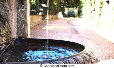 water flowing at the street fountain at the small italian...