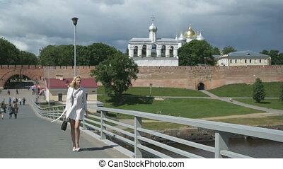 Pretty elegant woman walking along bridge - Beautiful blonde...