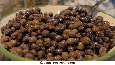 Bowl is full with marinated olives - Close-up shot of a big...