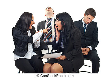 Women laughing and pointing to asleep men - Businesswomen...