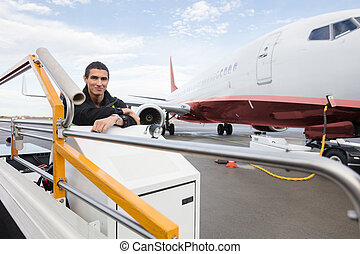Confident Male Worker Sitting On Luggage Conveyor Truck -...