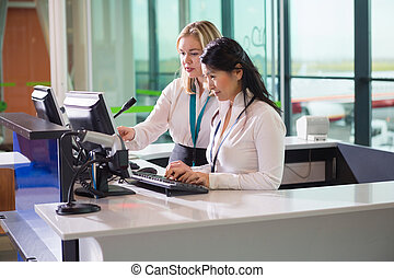 Female Ground Staff Using Computer At Counter In Airport -...