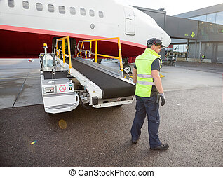Worker Standing By Luggage Conveyor Attached To Airplane -...