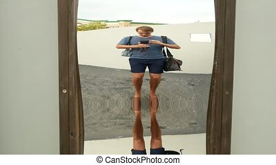 a man takes his reflection in a false mirror on the camera....