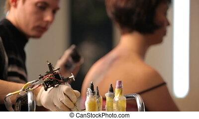 Girl get a tattoo - Create a beautiful tattoo in a tattoo...