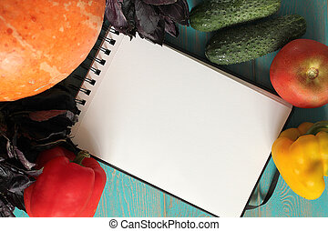 Note book and composition of vegetables on blue wooden desk....